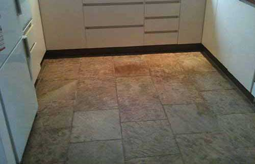 unsleaed clean slate tiles in kitchen floor with white cupboards